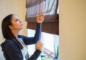 pic of jalousie  - Young woman opening jalousie in her apartment - JPG