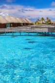 Luxury resort in Maldives, little wooden bungalows over blue transparent water, spending summer vaca