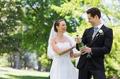 Young newlywed couple opening champagne bottle in park