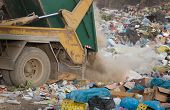 stock photo of junk-yard  - Truck tipping garbage from container on junk yard - JPG