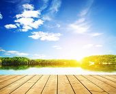 stock photo of board-walk  - Sunset on forest lake and wooden board background  - JPG