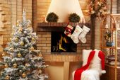 stock photo of christmas wreaths  - Christmas room with fireplace chair presents under decorated fir tree and toys in it - JPG