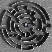 Top view of successful businessman standing in center of labyrinth