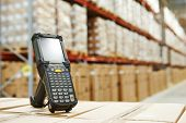 foto of warehouse  - Bluetooth barcode scanner in front of modern warehouse - JPG