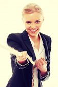 Businesswoman pulling on a piece of rope.