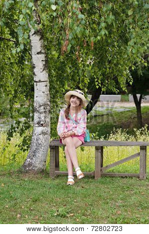 Happy girl sitting on a wooden bench under the birch tree