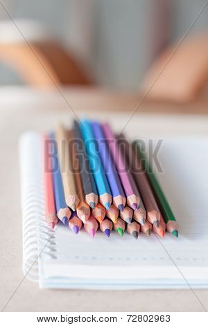 Colorful Pencil Crayons On Spiral Notebook