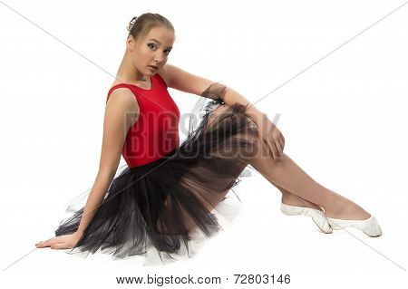 Photo of young ballerina sitting on the floor