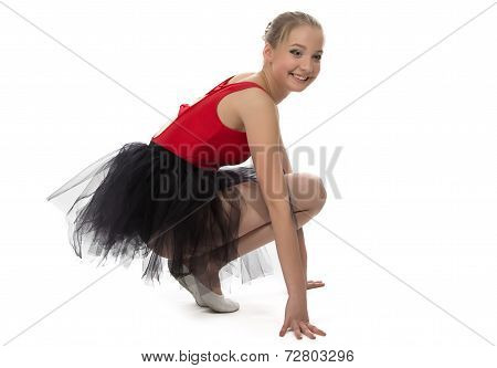 Yong ballerina sitting on haunches