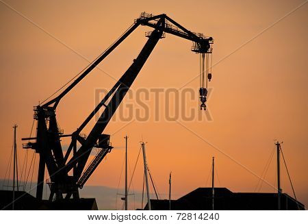 Silhouette dockside crane at sunset
