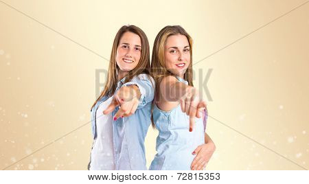 Girls Pointing To The Front Over Ocher Background