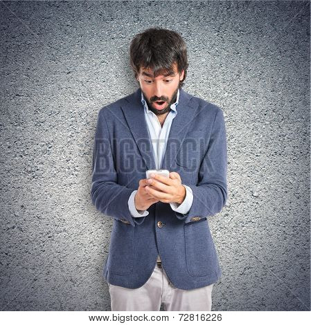 Surprised Man Talking To Mobile Over Textured Background