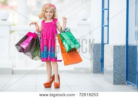 Little girl walking with shopping bags in store