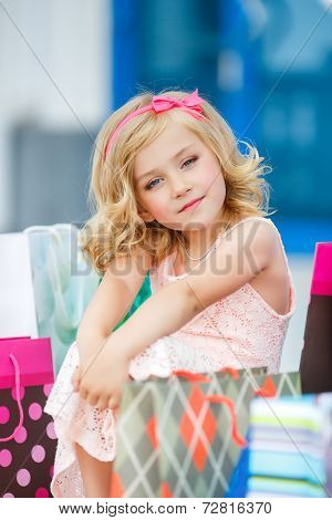 Cheerful girl of preschool age with bags goes to the store