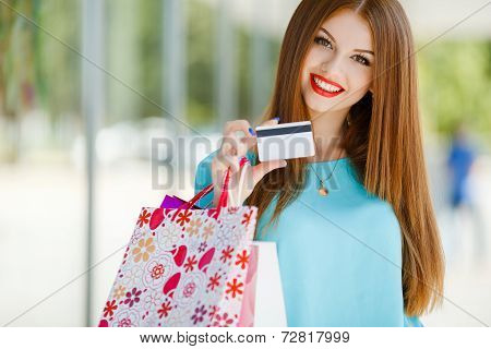Woman holding shopping bags and credit card at shopping mall