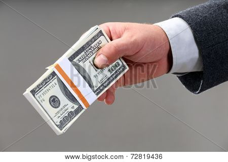 Male Hand Holding A Wad Of Hundred Dollar Bills