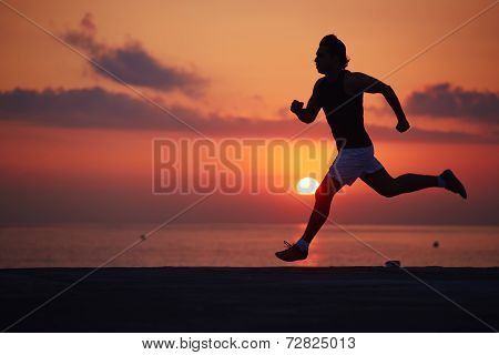 Athletic build jogger running with high speed, silhouette of runner in action running along the beac