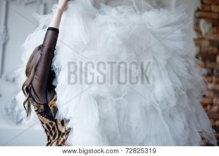 The girl lifts a hem from a wedding dress
