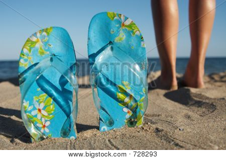 Sandals And Legs On The Beach