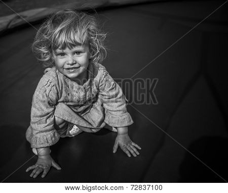 Adorable Blonde Toddler Girl Sitting On A Trampoline