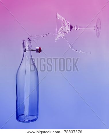 Clear Water Pour Horizontal Out Of Bottle Splash Into Glass With Blue And Pink Back Lighting