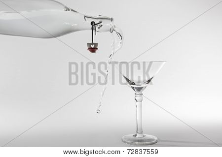 Clear Water Pour Out Of Bottle Splash Into Glass And Spill With Grey Back Lighting