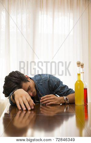 Young Man Drunk And Sleeping Alone At A Table With Two Bottles Of Liquor