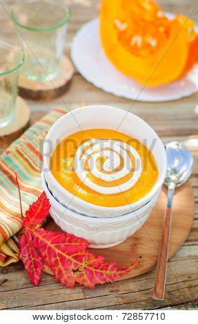 Pumpkin Cream Soup With Sour Cream In A White Bowl