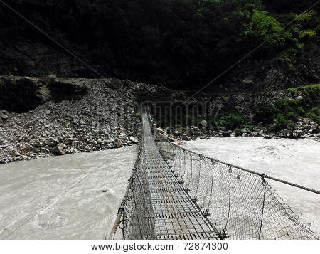 Traditional Suspension Bridge Crossing A Wild River