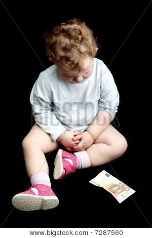 Curly baby looking down at some money isolated on black