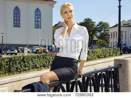 Girl Sitting On Architecture Background
