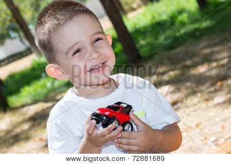 Cute Little Child Boy Plays With Toy Car In Park On Nature At Summer. Use It For Baby, Parenting Or