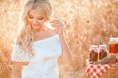 stock photo of carnal  - The beautiful blond woman has a rest among a field of ripe wheat in a summer sunny day - JPG