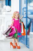 pic of curio  - Cheerful preschool girl walking with shopping bags - JPG