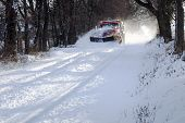 stock photo of tree lined street  - A snowplow truck removing snow from a tree lined rural road on a cold winter day - JPG
