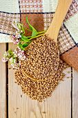 picture of buckwheat  - Buckwheat in a spoon with flower buckwheat napkin on background of wooden boards - JPG