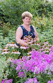 foto of meadowsweet  - mature woman with flowers at a garden - JPG