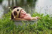 picture of yawn  - A yawning three month old baby boy wearing a crocheted puppy dog hat - JPG