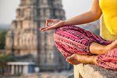 stock photo of karnataka  - Woman doing meditation near Virupaksha temple in Hampi Karnataka India - JPG