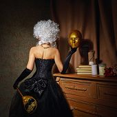 stock photo of tight dress  - Young attractive courtesan in a lush wig and dressed in a tight fitting corset dress - JPG