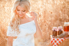 picture of carnal  - The beautiful blond woman has a rest among a field of ripe wheat in a summer sunny day - JPG