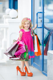 picture of curio  - Cheerful preschool girl walking with shopping bags - JPG
