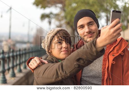 Young Couple Having Fun With Mobile Photography