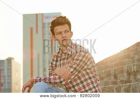 Handsome man outdoors sitting on stone stairs