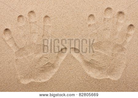 Imprint Of Two Human Hands In The Sand