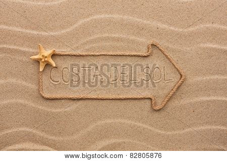 Arrow Made Of Rope And Sea Shells With The Word Costa Del Sol On The Sand