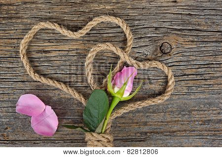 pink rose bud with rope hearts