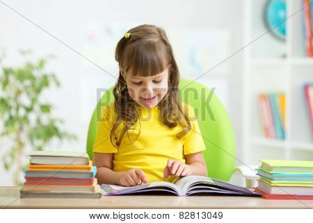 Happy child learning to read in nursery