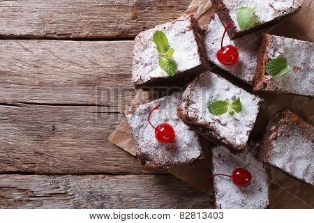 Brownie Cake With Mint And Cherry On Paper Horizontal Top View