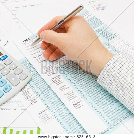 Male Filling Out 1040 Us Tax Form Using Silver Ball Pen